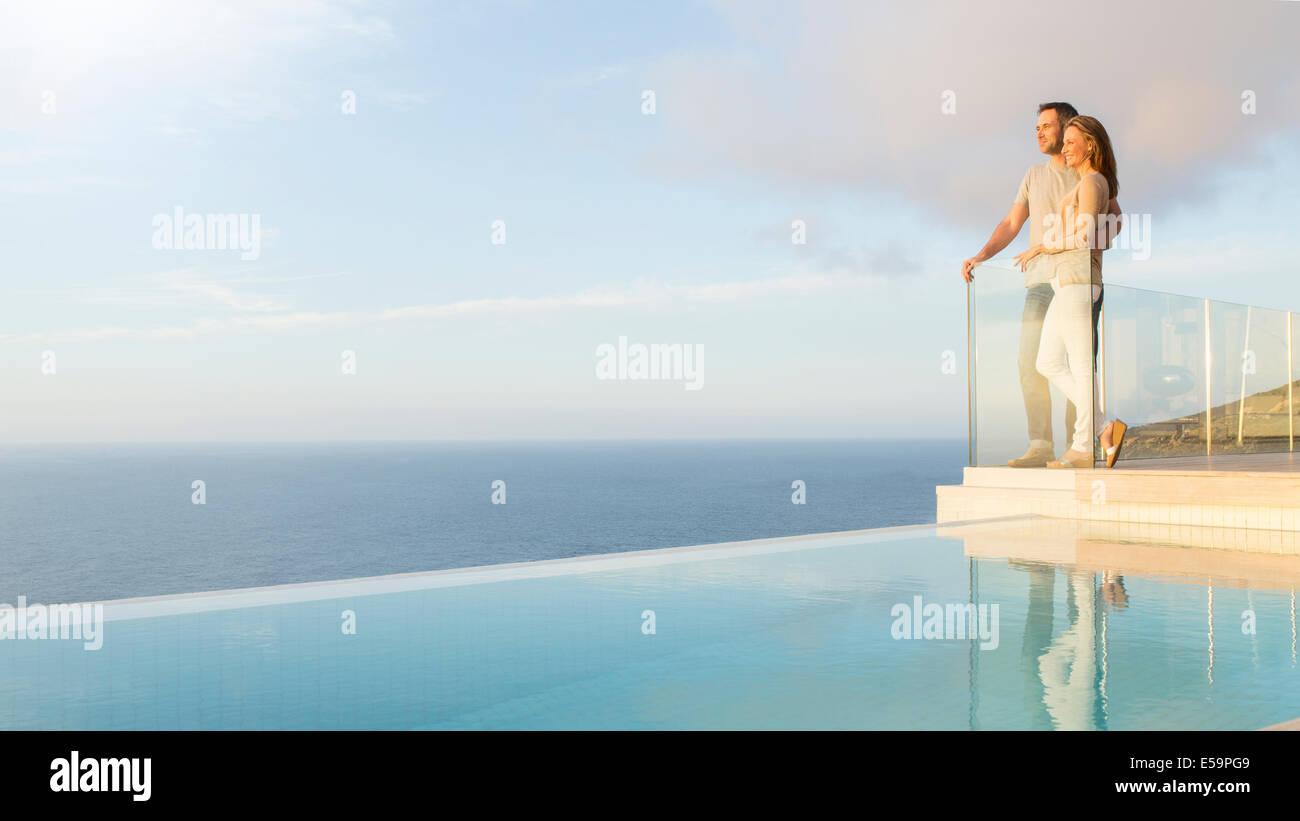 Giovane con vista sull'oceano dal balcone moderno Immagini Stock
