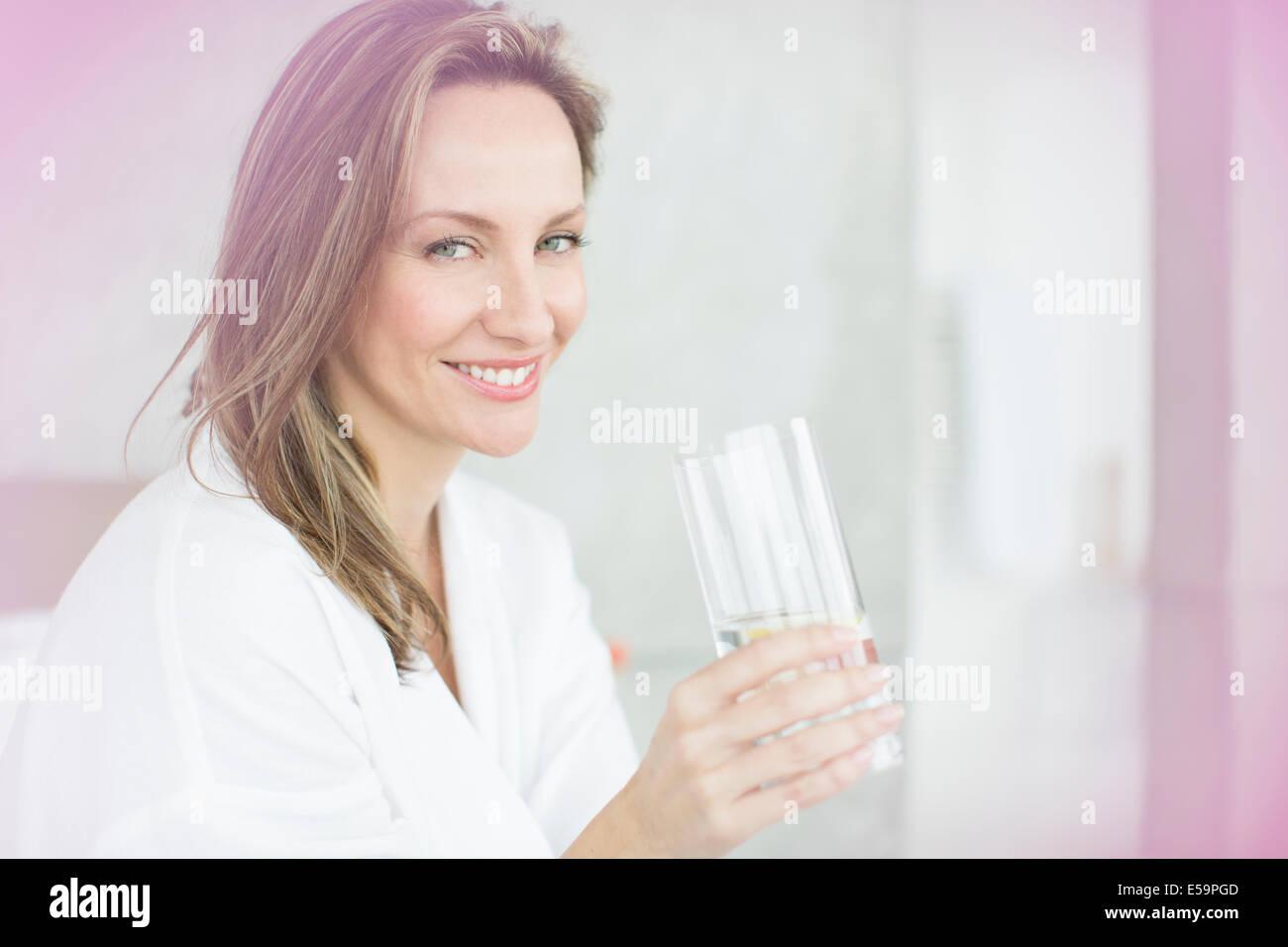 Donna con un bicchiere di acqua in camera da letto Immagini Stock