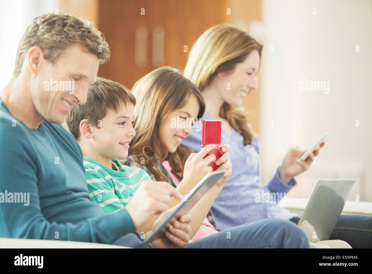 La famiglia utilizzando la tecnologia sul divano Foto Stock