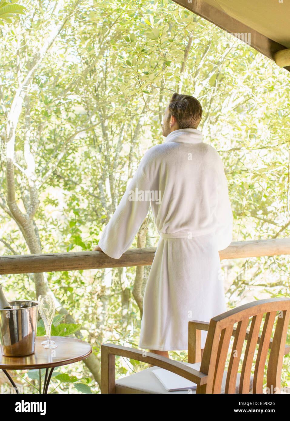 Uomo di indossare accappatoio sul balcone Immagini Stock