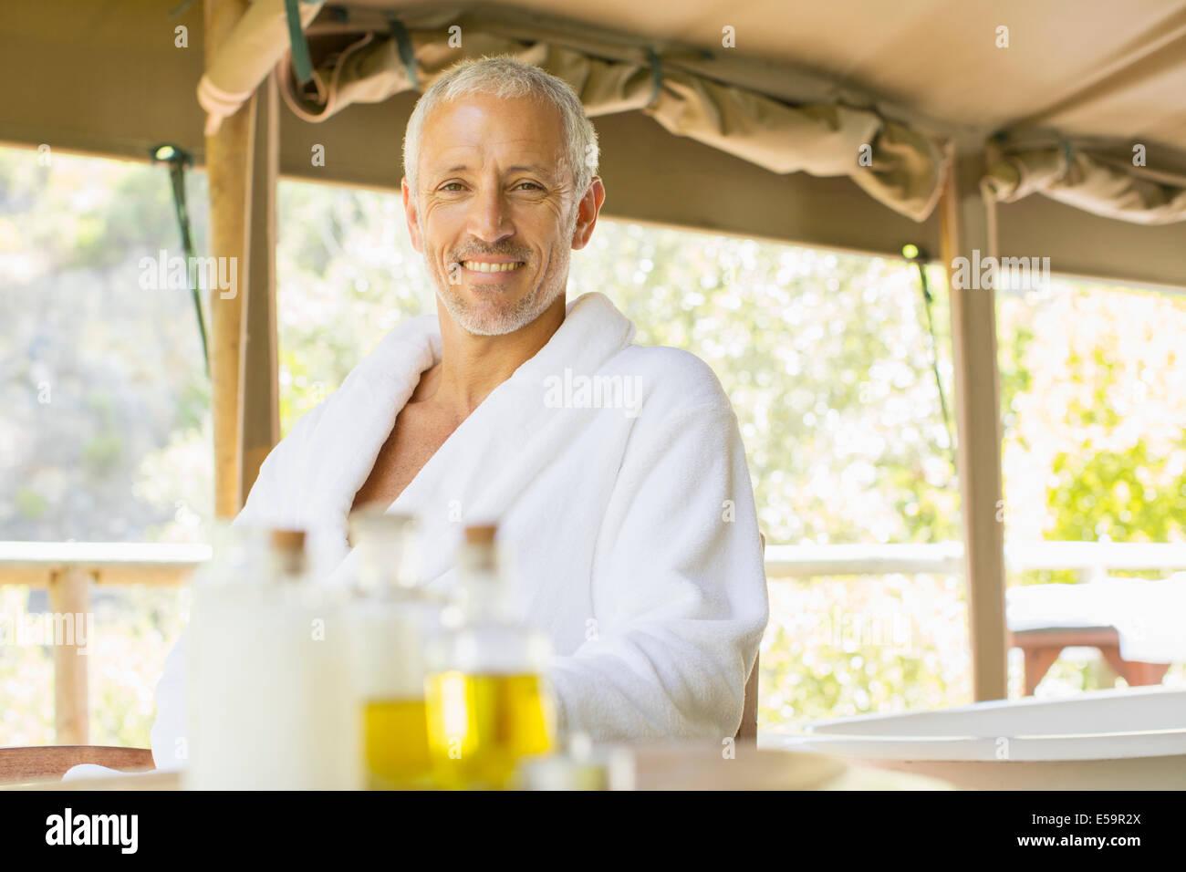 Uomo di indossare accappatoio a tavola Immagini Stock