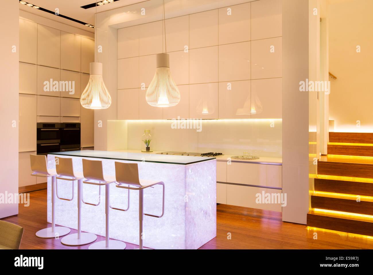 Sgabelli da bar e illuminazione nella cucina moderna foto