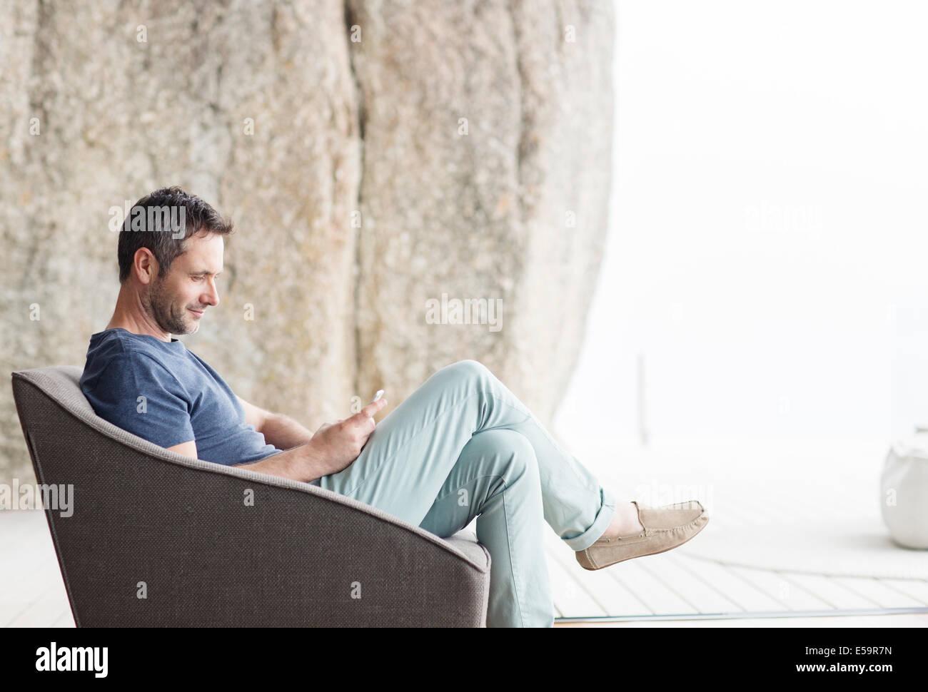 Uomo seduto in poltrona moderna Immagini Stock