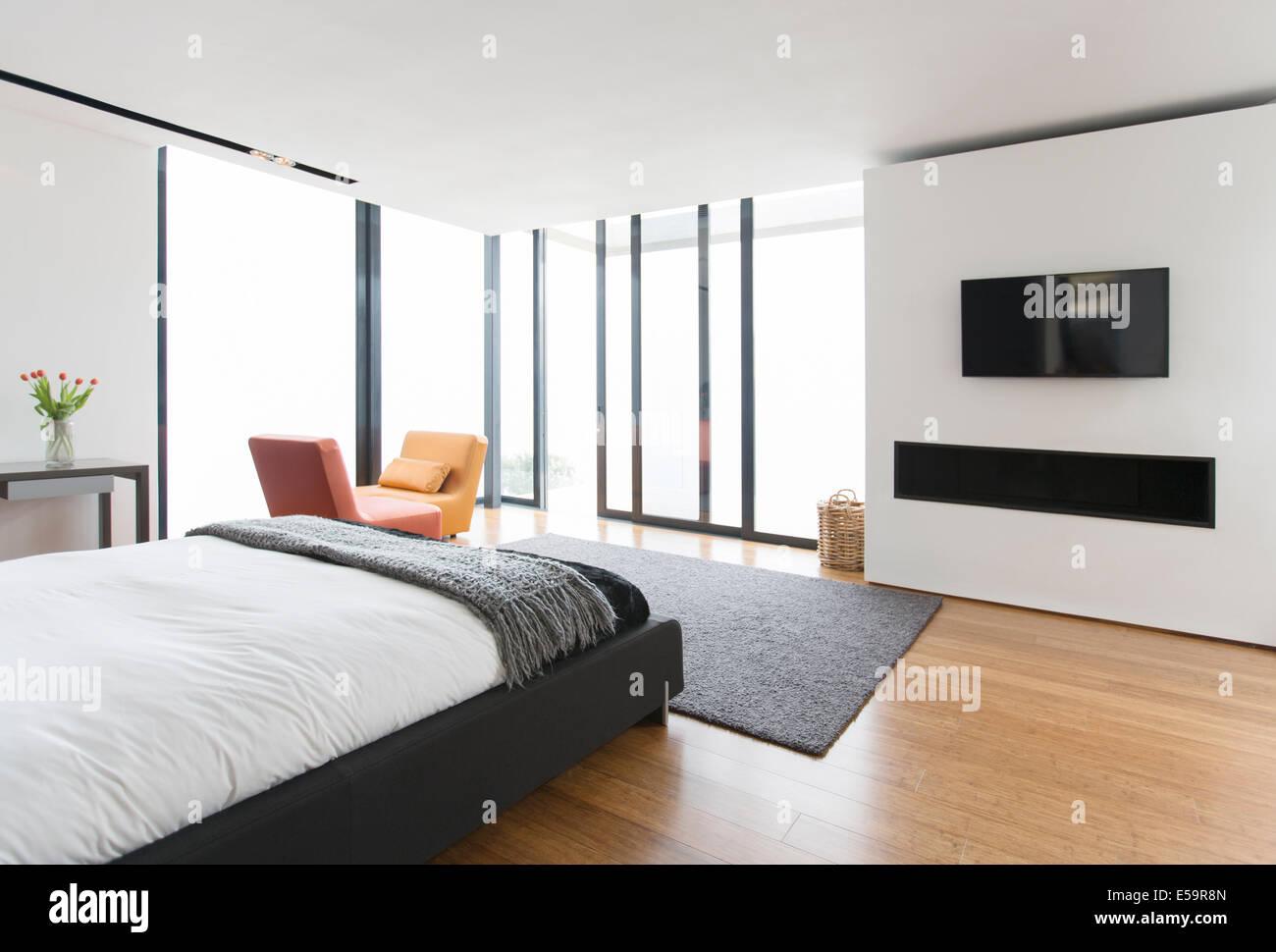 Letto e porte scorrevoli in vetro nella camera da letto moderna Immagini Stock