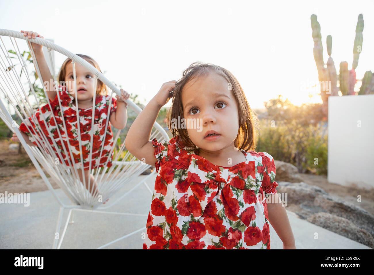 Twin baby ragazze giocando sul patio Immagini Stock