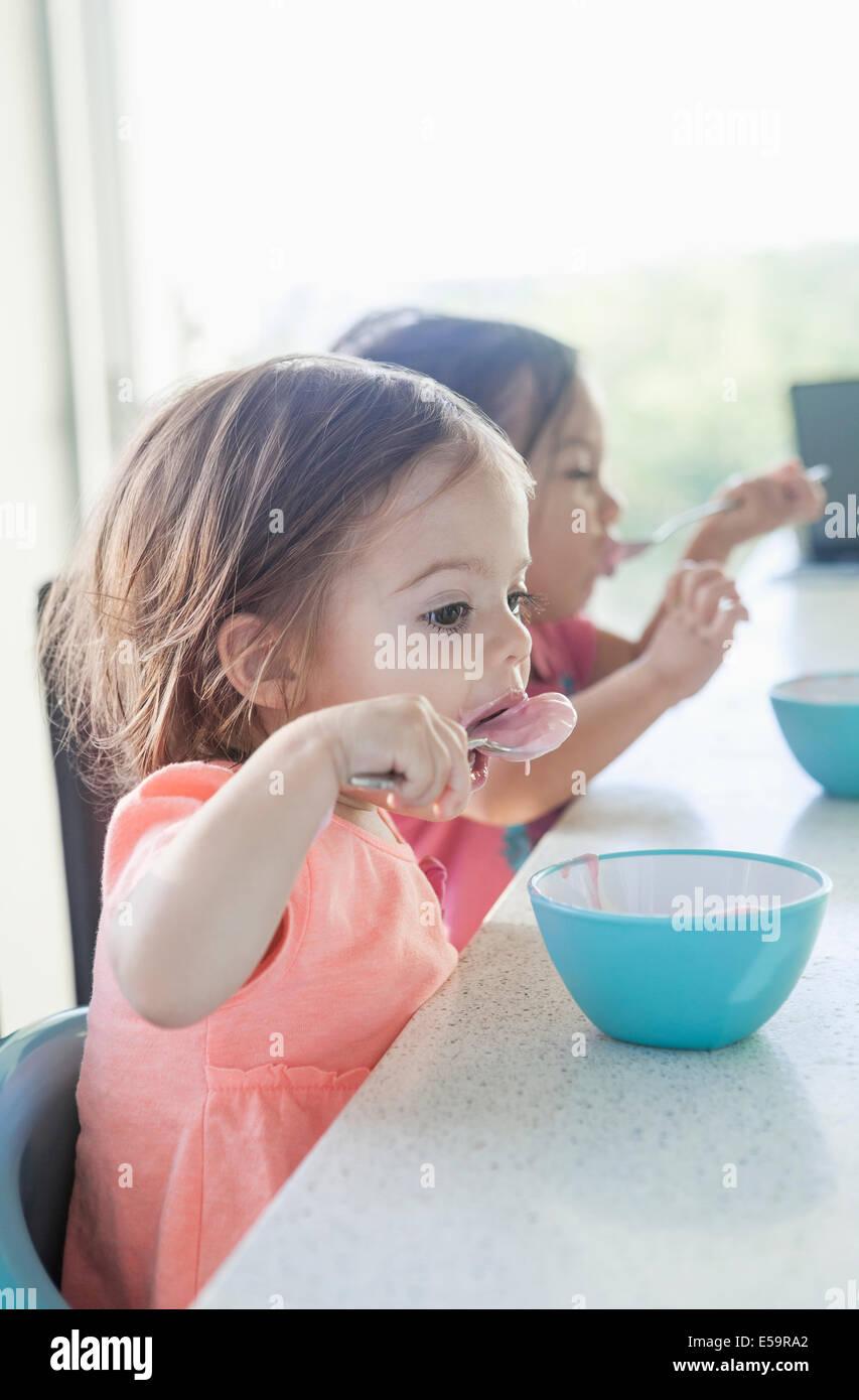 Sorelle di mangiare insieme per la prima colazione Immagini Stock