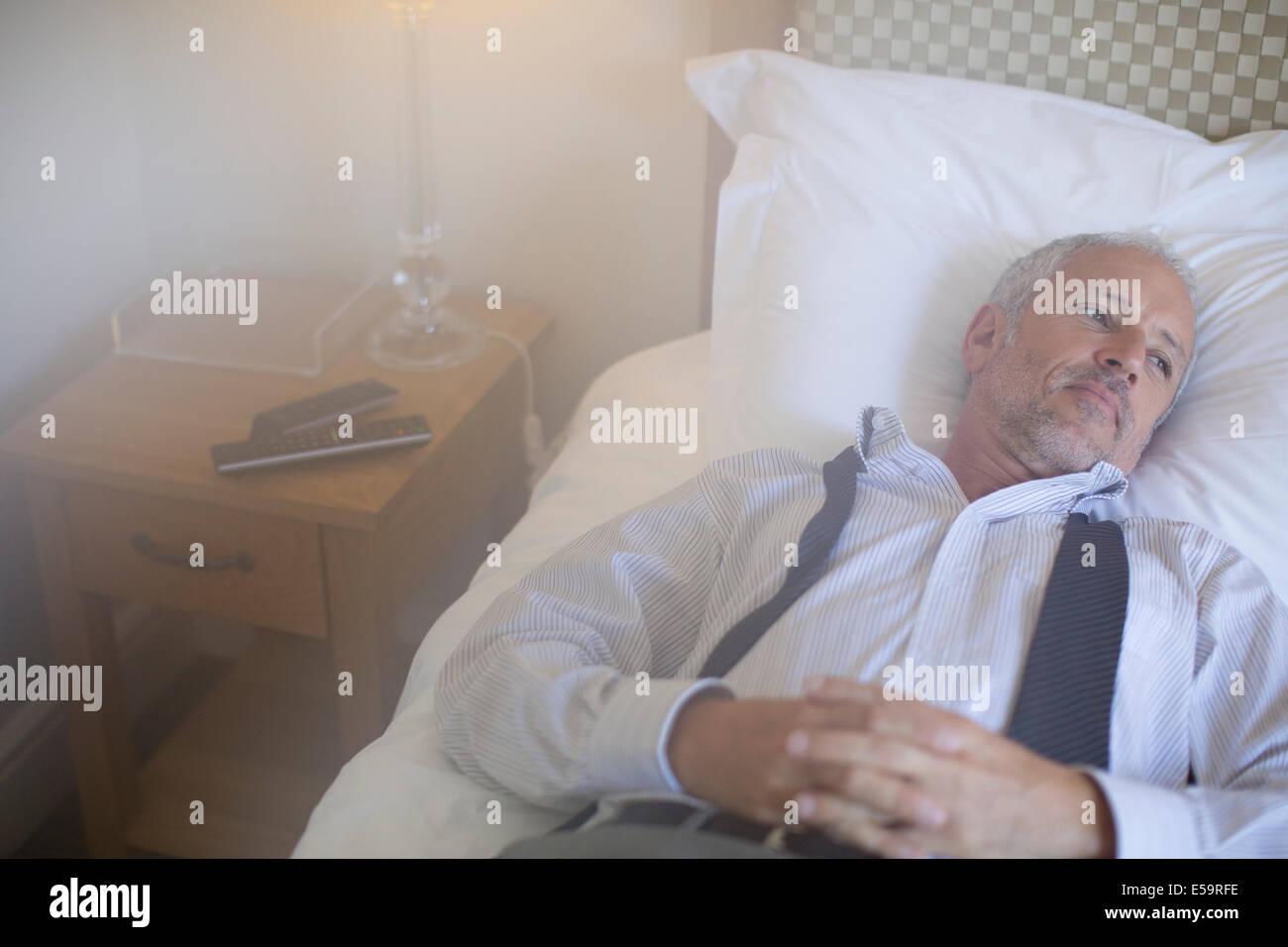Imprenditore rilassante sul letto in camera di albergo Immagini Stock