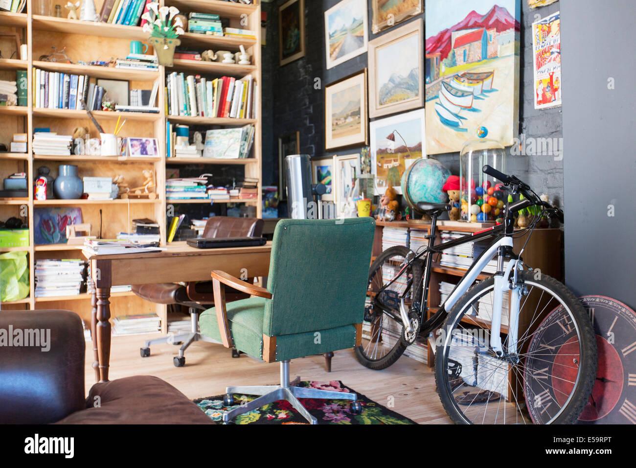 Scrivania, librerie e bicicletta in studio Immagini Stock