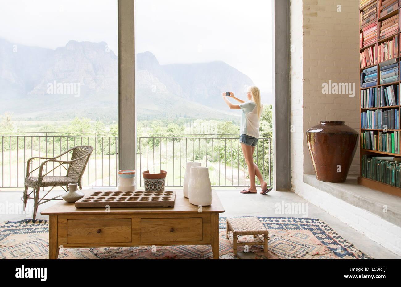 La donna sta immagine di panorama dal balcone Immagini Stock