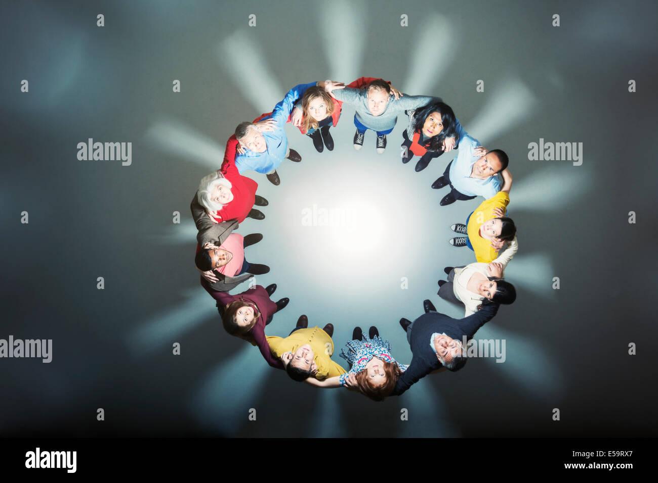 La gente di affari formando huddle intorno a una luce brillante Immagini Stock