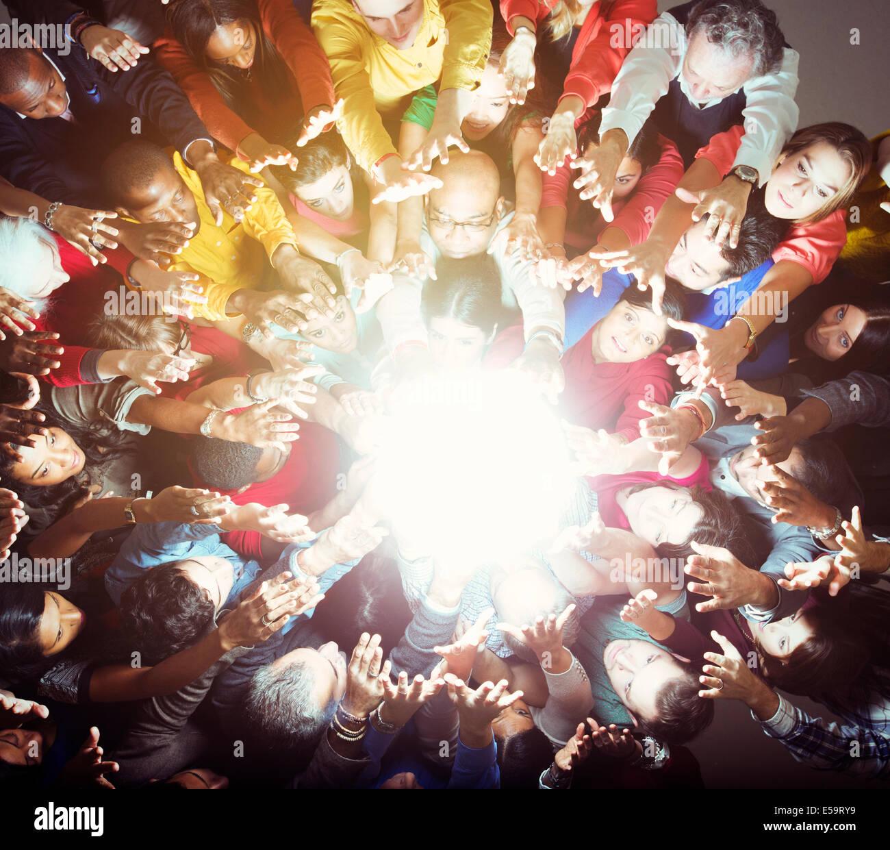 Folla variegata raggiungendo per la brillante luce Immagini Stock