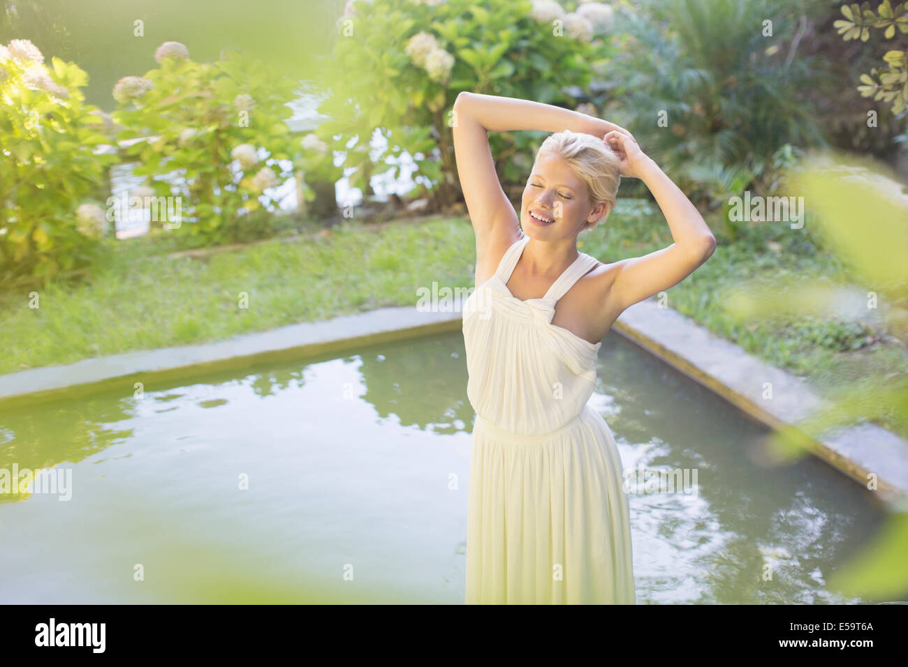 Donna in piedi dalla piscina all'aperto Immagini Stock