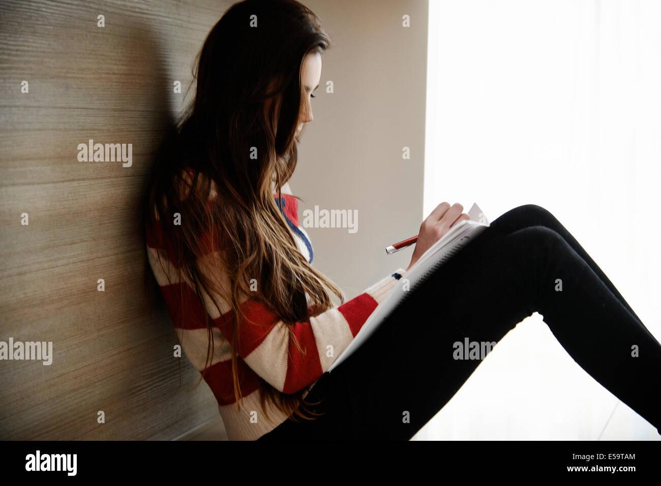 Ragazza adolescente iscritto nel notebook Immagini Stock
