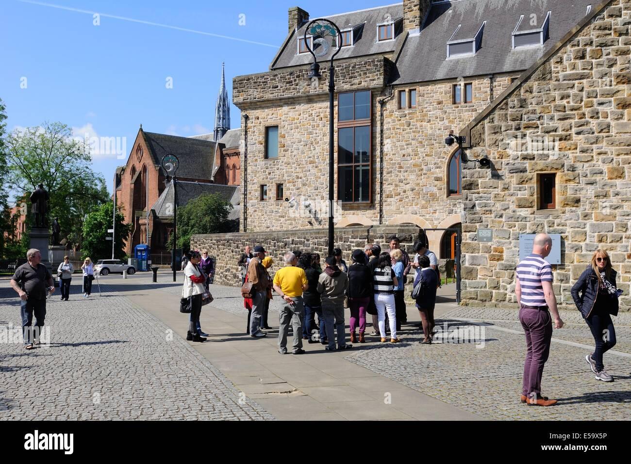 Una guida raduna il suo gruppo di turisti presso il Museo di arte religiosa e la vita a Glasgow, Scozia Immagini Stock