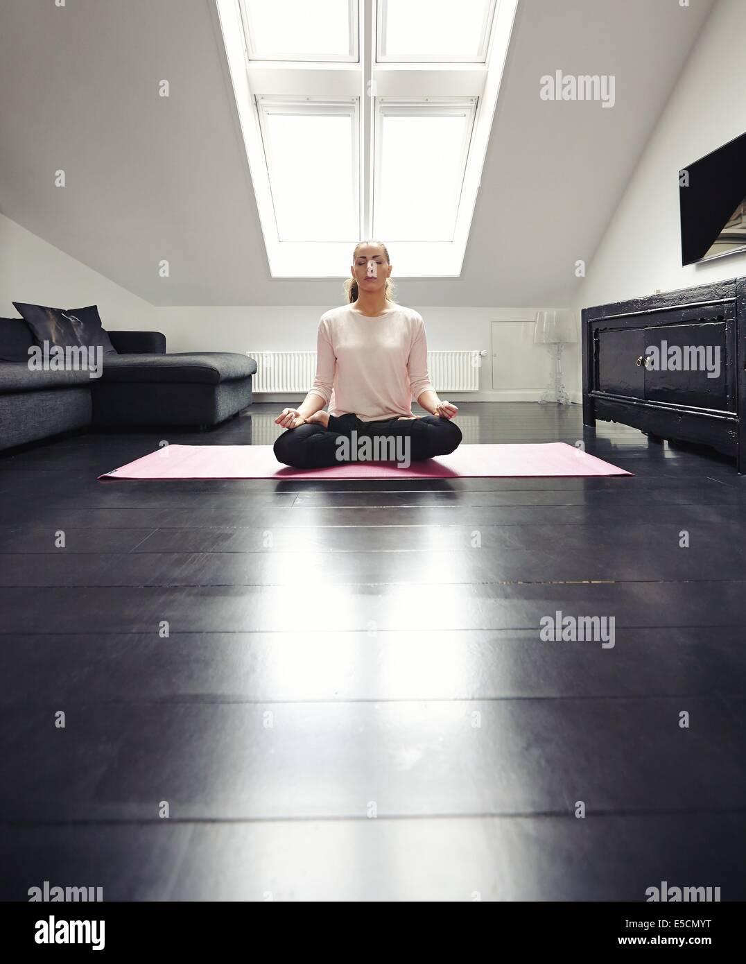 Signora giovane a praticare yoga nel suo salotto. Montare donna seduta sul pavimento meditando nella posizione del Immagini Stock