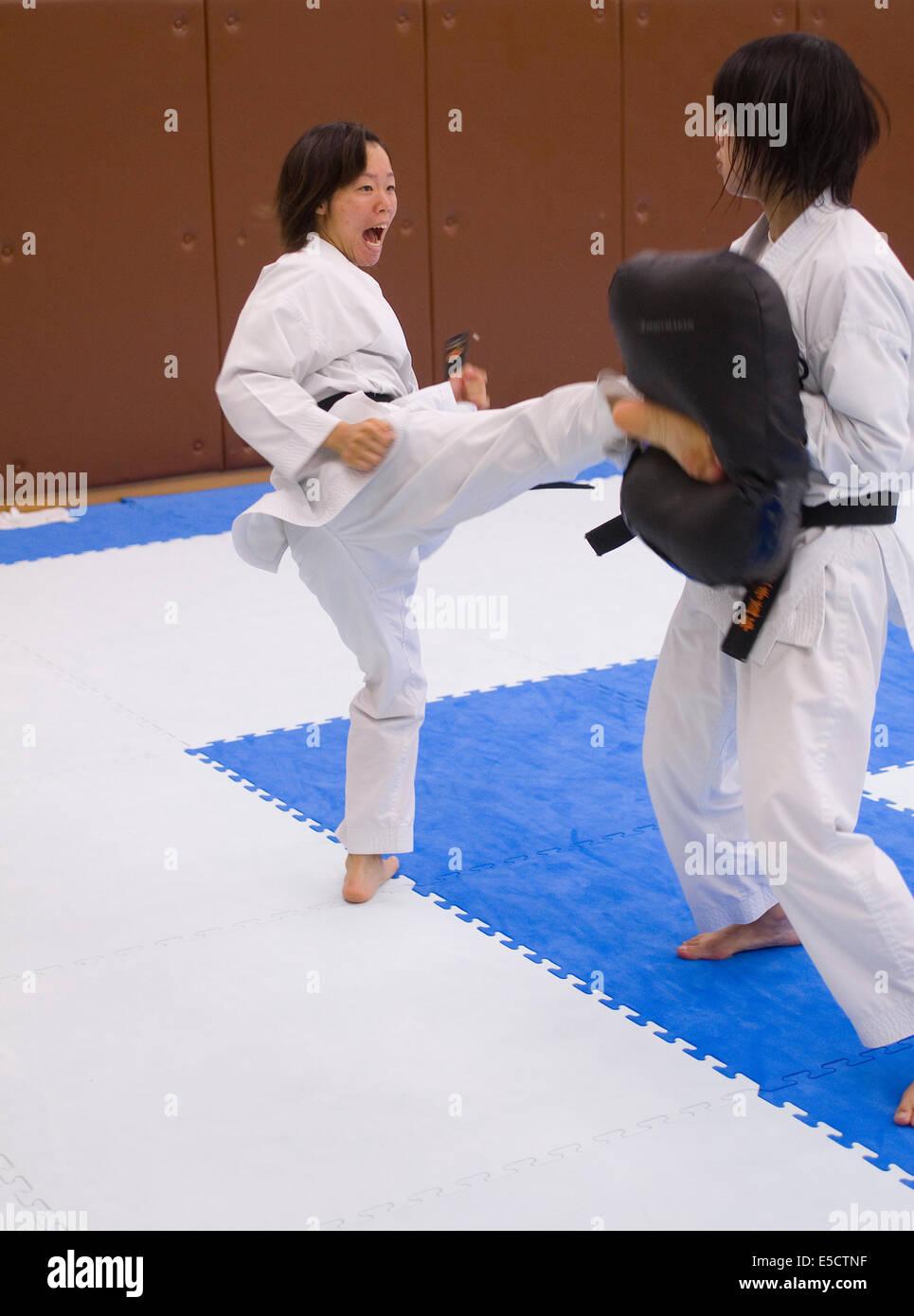 Gli adolescenti giapponesi a praticare il karate calci contro le pastiglie. Immagini Stock
