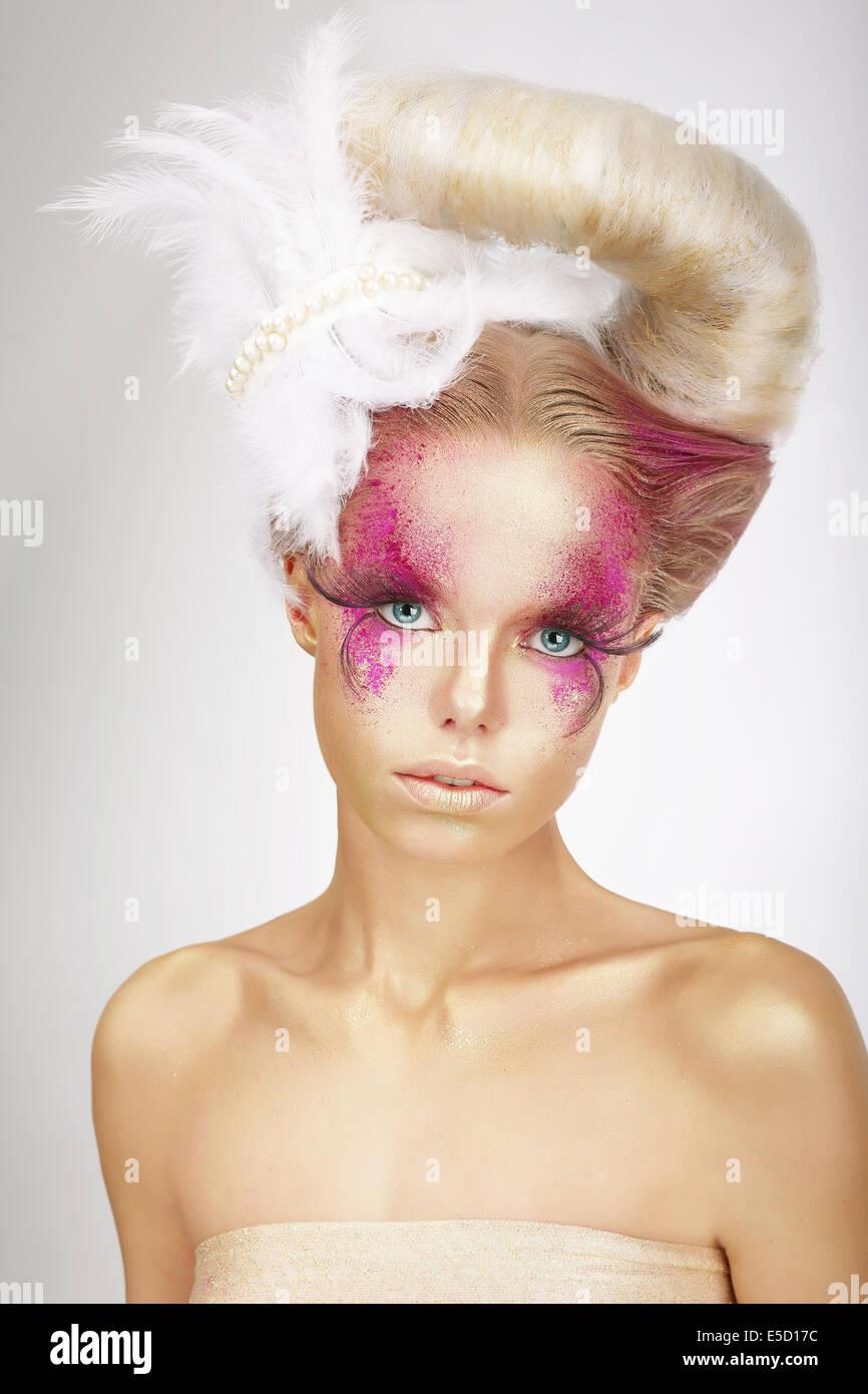 Faceart. Bionda con pelle colorato di rosa, Ciglia finte e piuma di colore bianco Immagini Stock