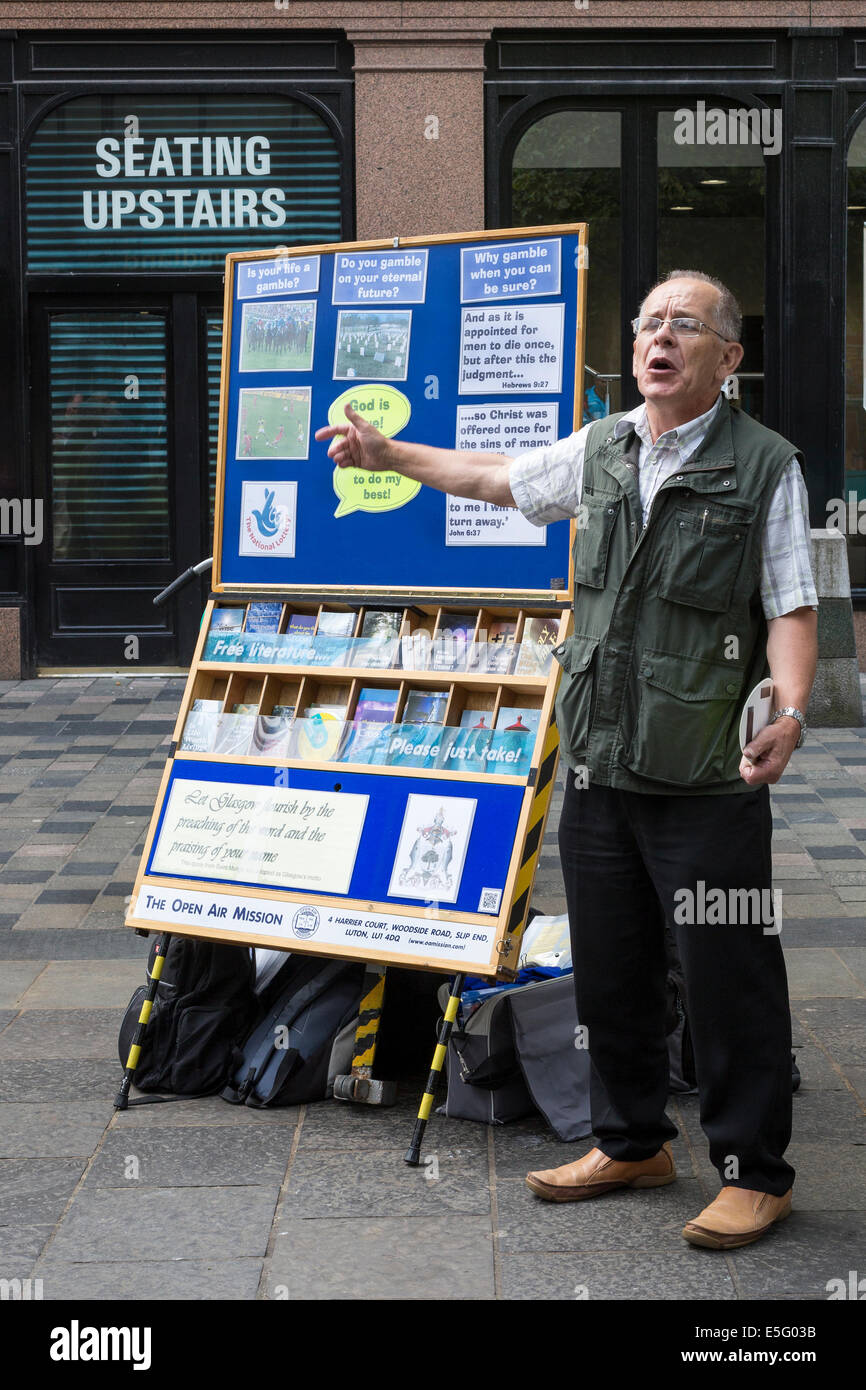 Street predicatore promuovere il cristianesimo e la vita eterna facendo riferimento a una bacheca, Sauchiehall Street, Immagini Stock
