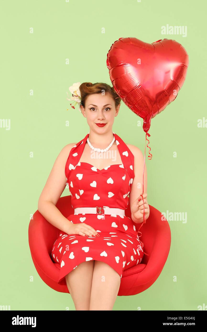 Donna in abito rosso di contenimento a forma di cuore palloncino Immagini Stock
