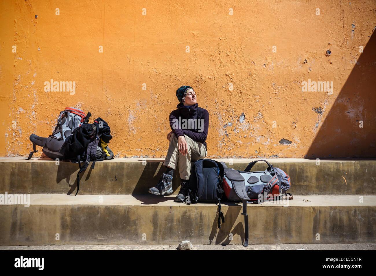 Ragazza in attesa con zaini in sun. Immagini Stock