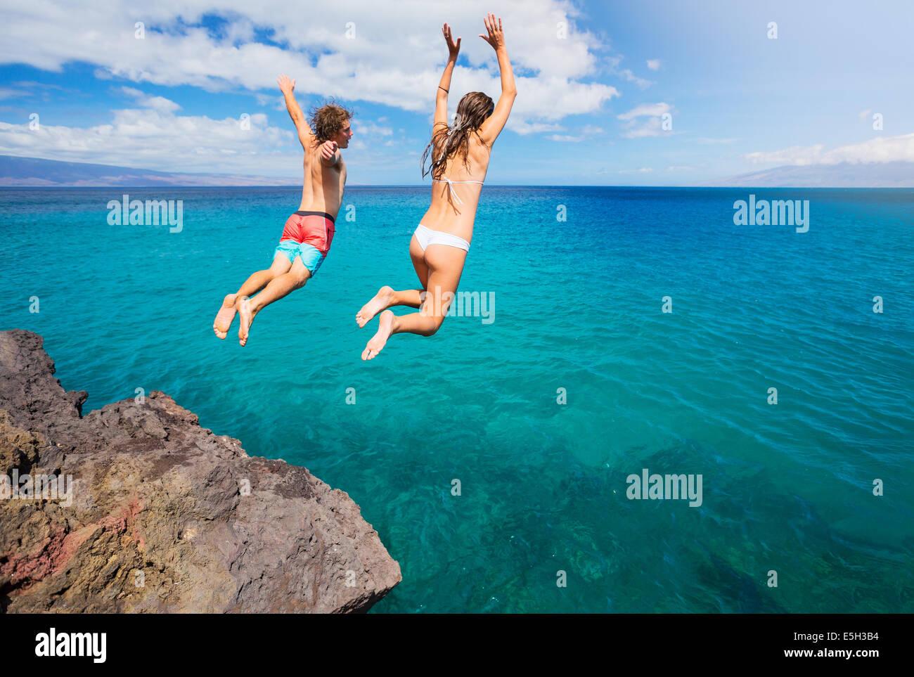 Amici cliff jumping nell'oceano, estate divertimento stile di vita. Immagini Stock