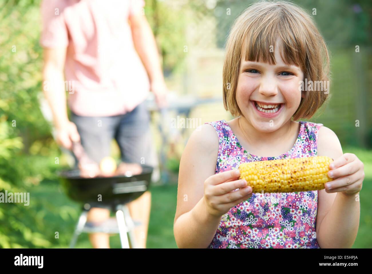 Ragazza giovane mangiare Granturco dolce al barbecue di famiglia Immagini Stock