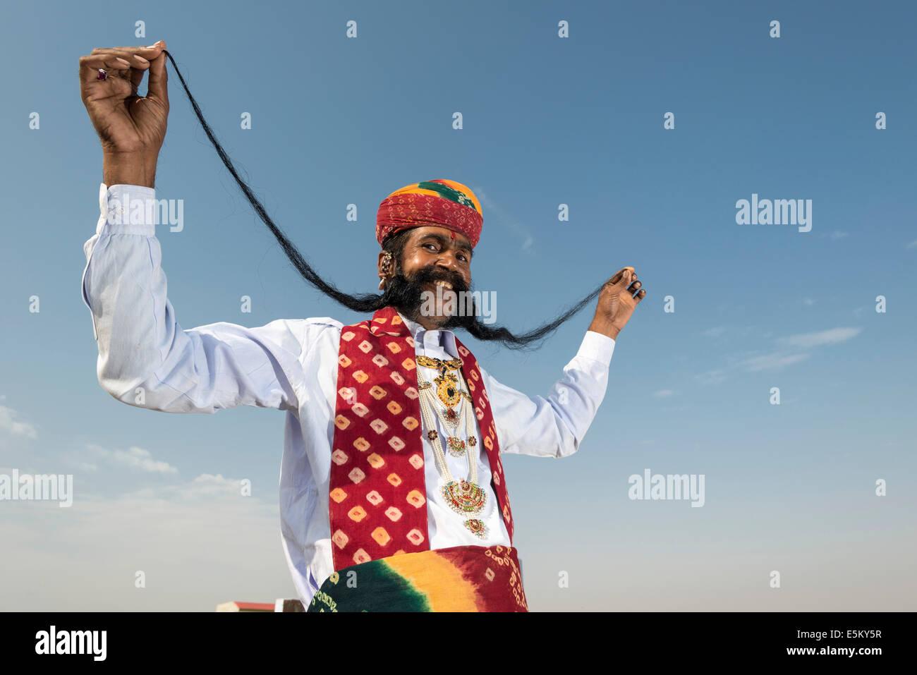 Uomo locale presentando il suo lungo i baffi, Rajput persone, Bikaner, Rajasthan, India Foto Stock