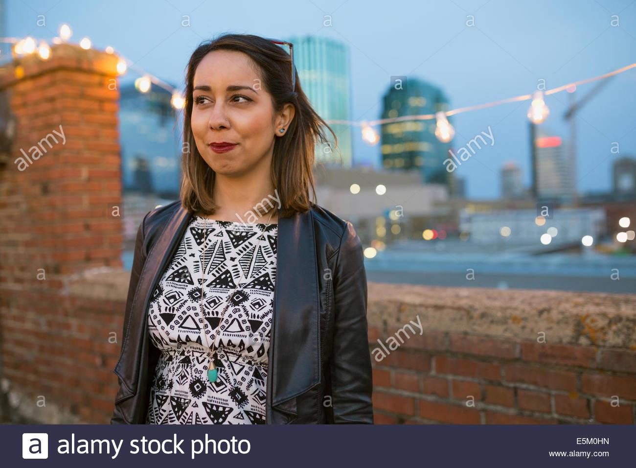 Donna sorridente che guarda lontano sul tetto urbano Foto Stock