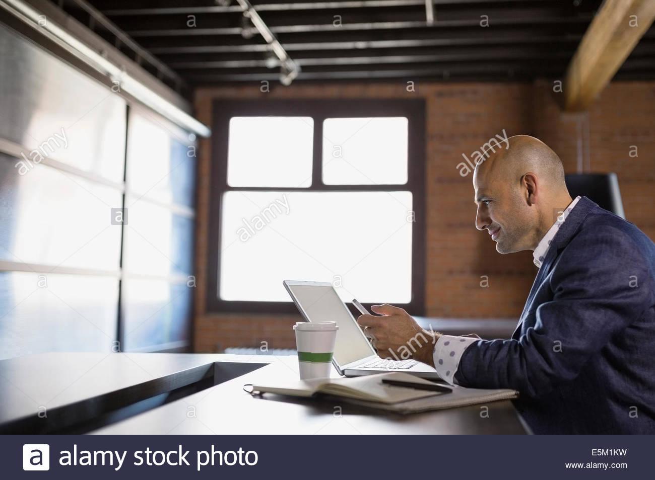 Uomo d affari con computer portatile e un telefono cellulare in cafe Immagini Stock