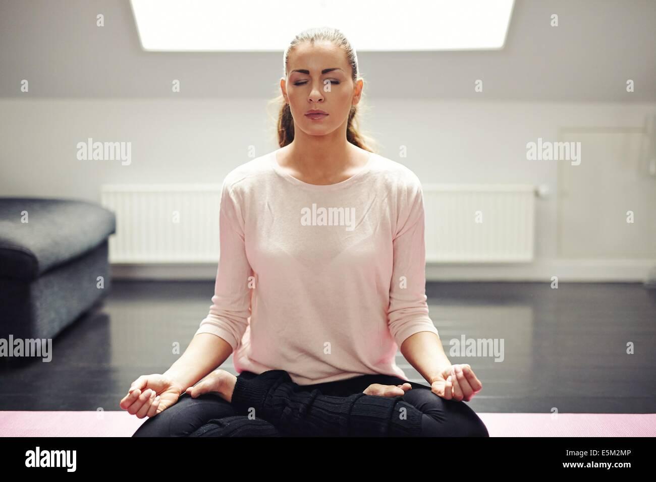 Ritratto di donna bella esercitazione. In un momento di relax a casa con lo yoga allenamento. Montare caucasian Immagini Stock