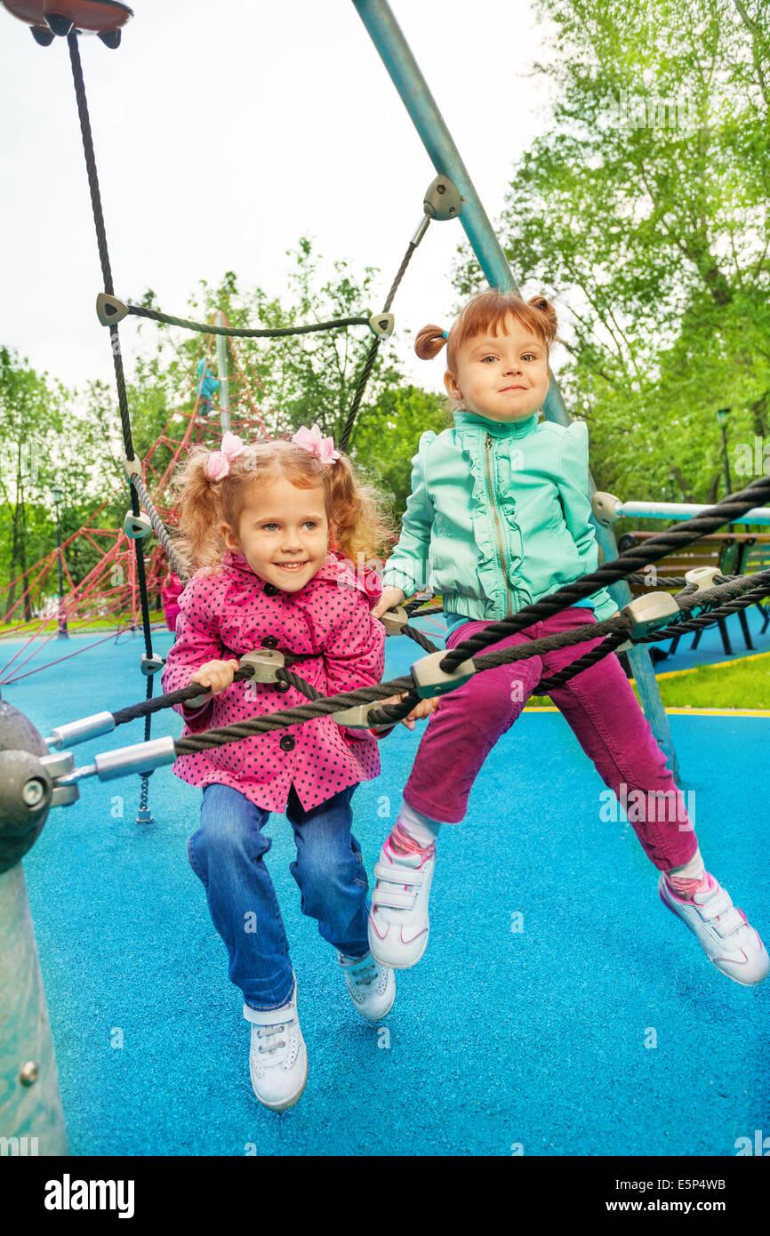Due ragazze divertente insieme sulla griglia del parco giochi Immagini Stock