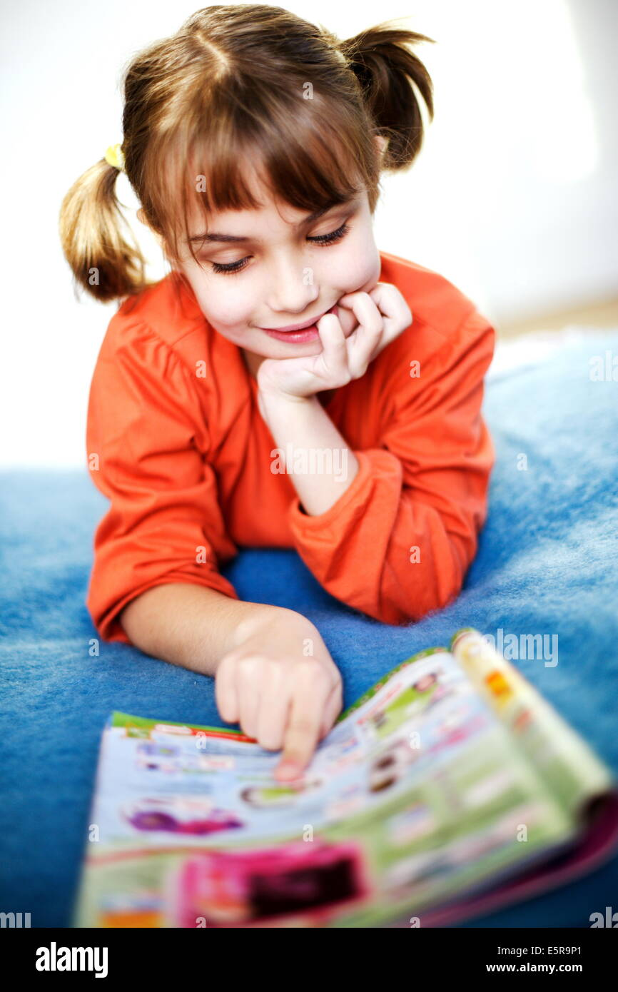 7 anno vecchia ragazza di lettura catalogo giocattolo. Immagini Stock