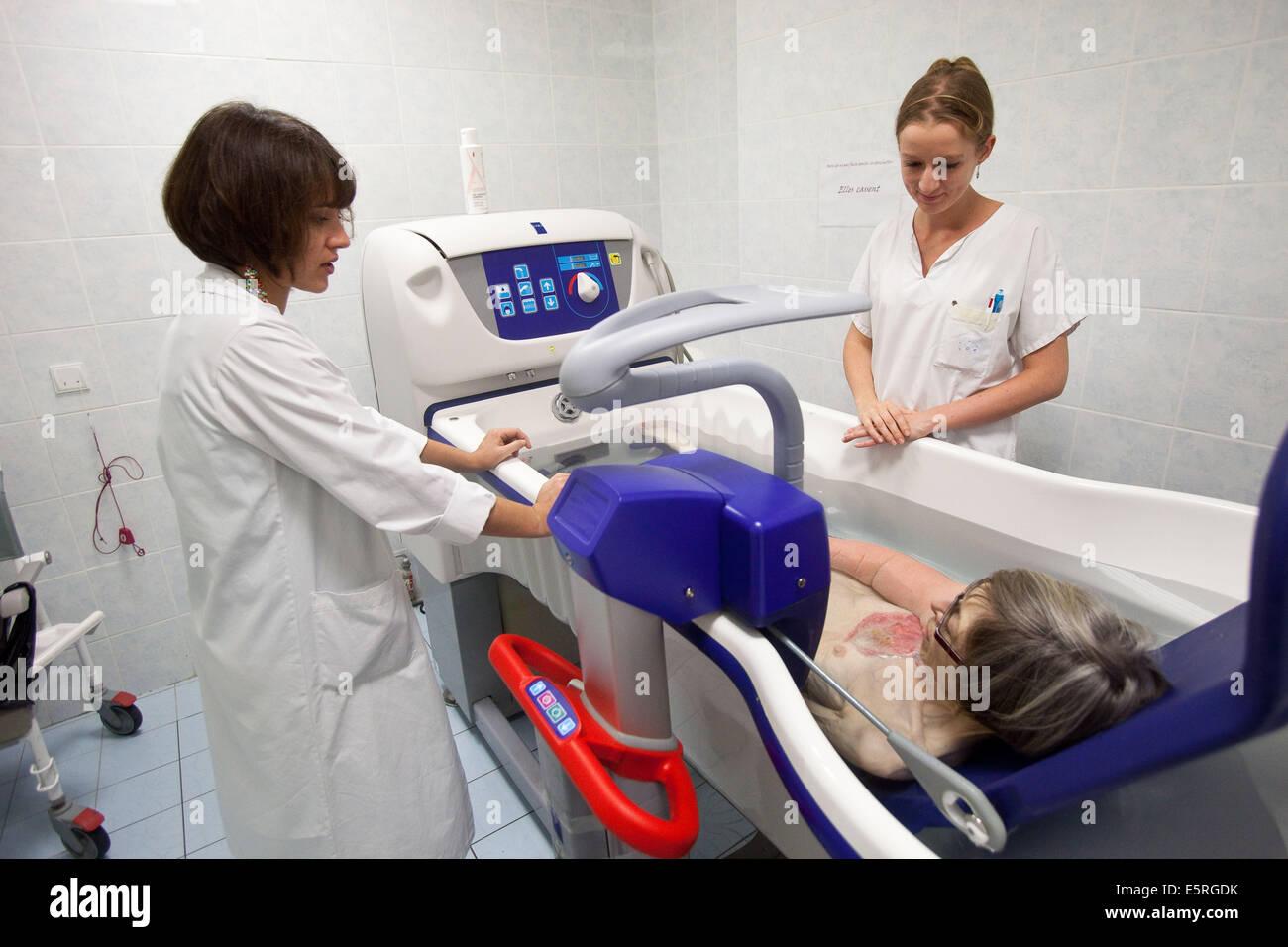 Gli infermieri bagno un paziente in una vasca da bagno ad