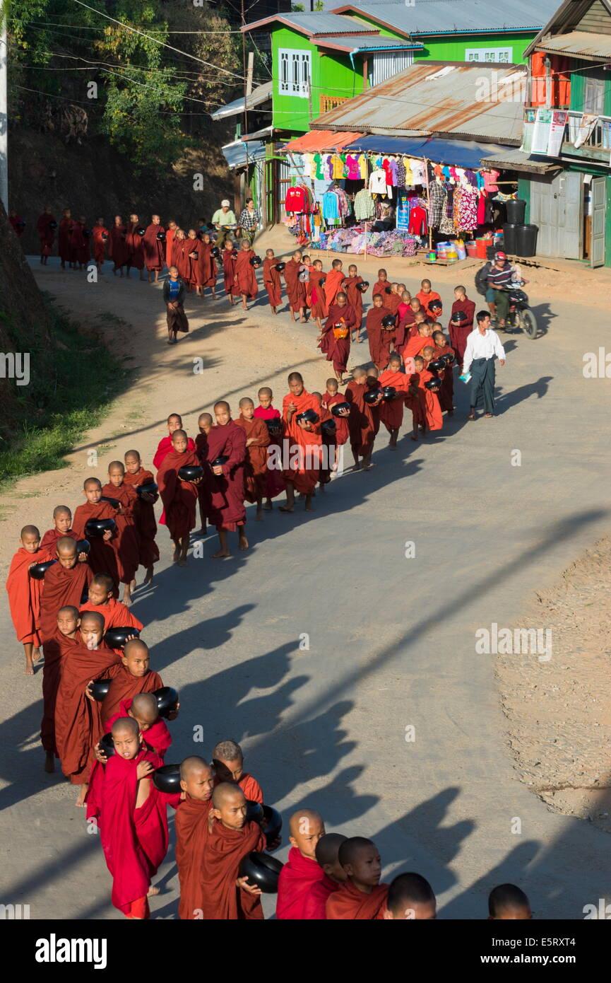 La abbott del monastero Taungpulu (U Pyinnya Thiri), portando il debuttante monaci in ALMS raccolta di mattina attraverso Immagini Stock