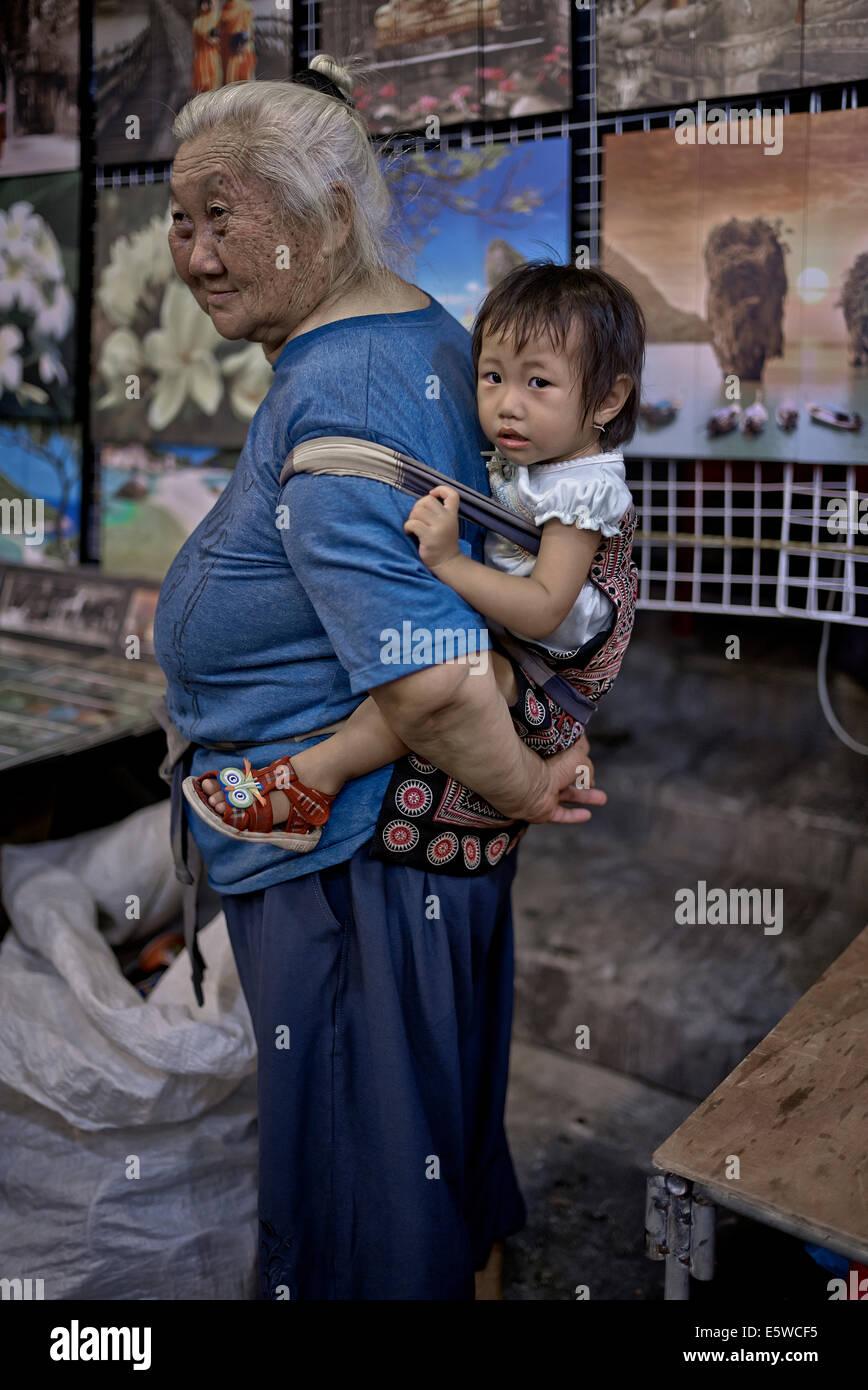 Nonna tailandese che trasportano neonato nipote in una imbragatura posteriore elettrico. Thailandia S. E. Asia, Immagini Stock