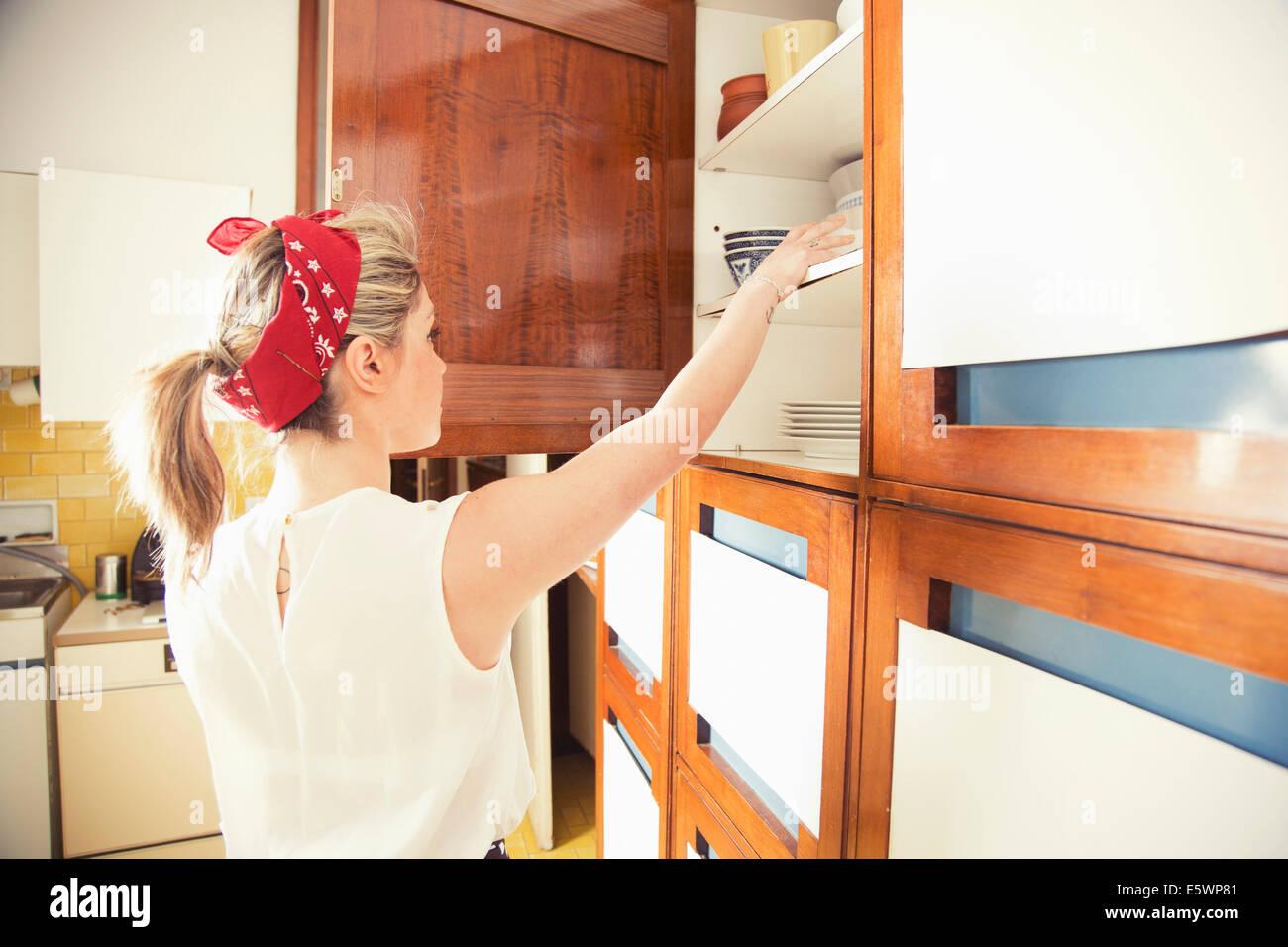 Credenza Vintage Per Cucina : Giovane donna raggiungendo per la credenza in cucina vintage foto