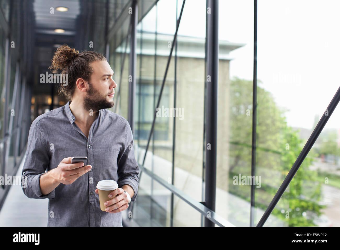 Uomo con lo smartphone su Pausa caffè Immagini Stock