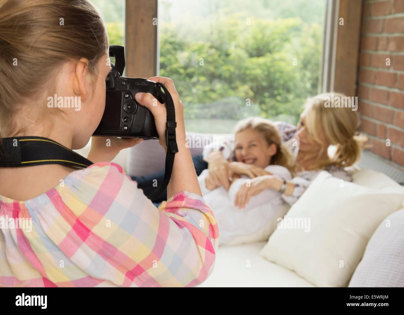 Figlia di prendere fotografia di madre e sorella Immagini Stock