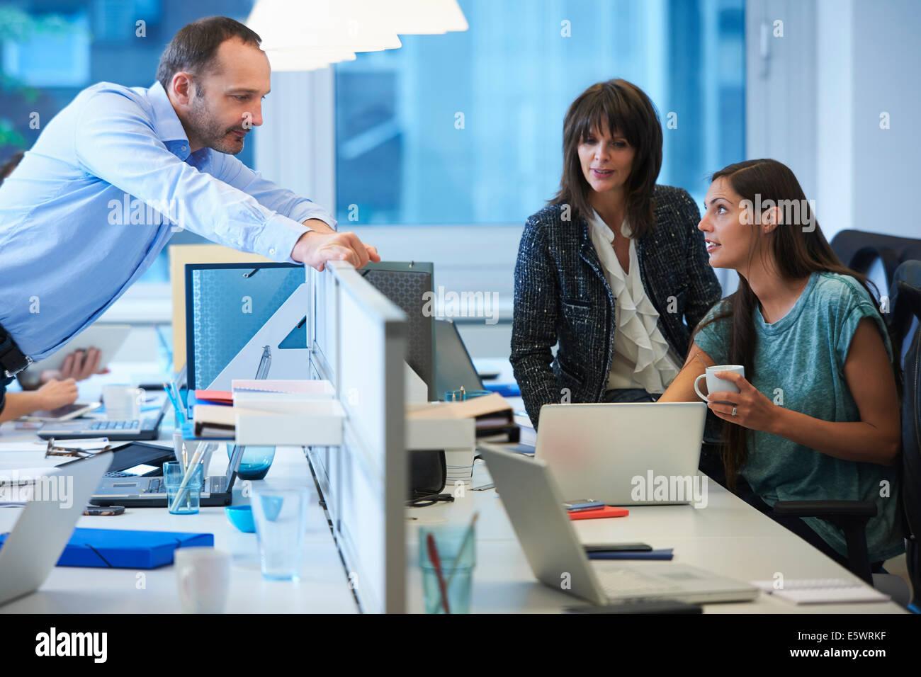 Uomo appoggiato sopra lo schermo divisorio, parlando con i colleghi Immagini Stock