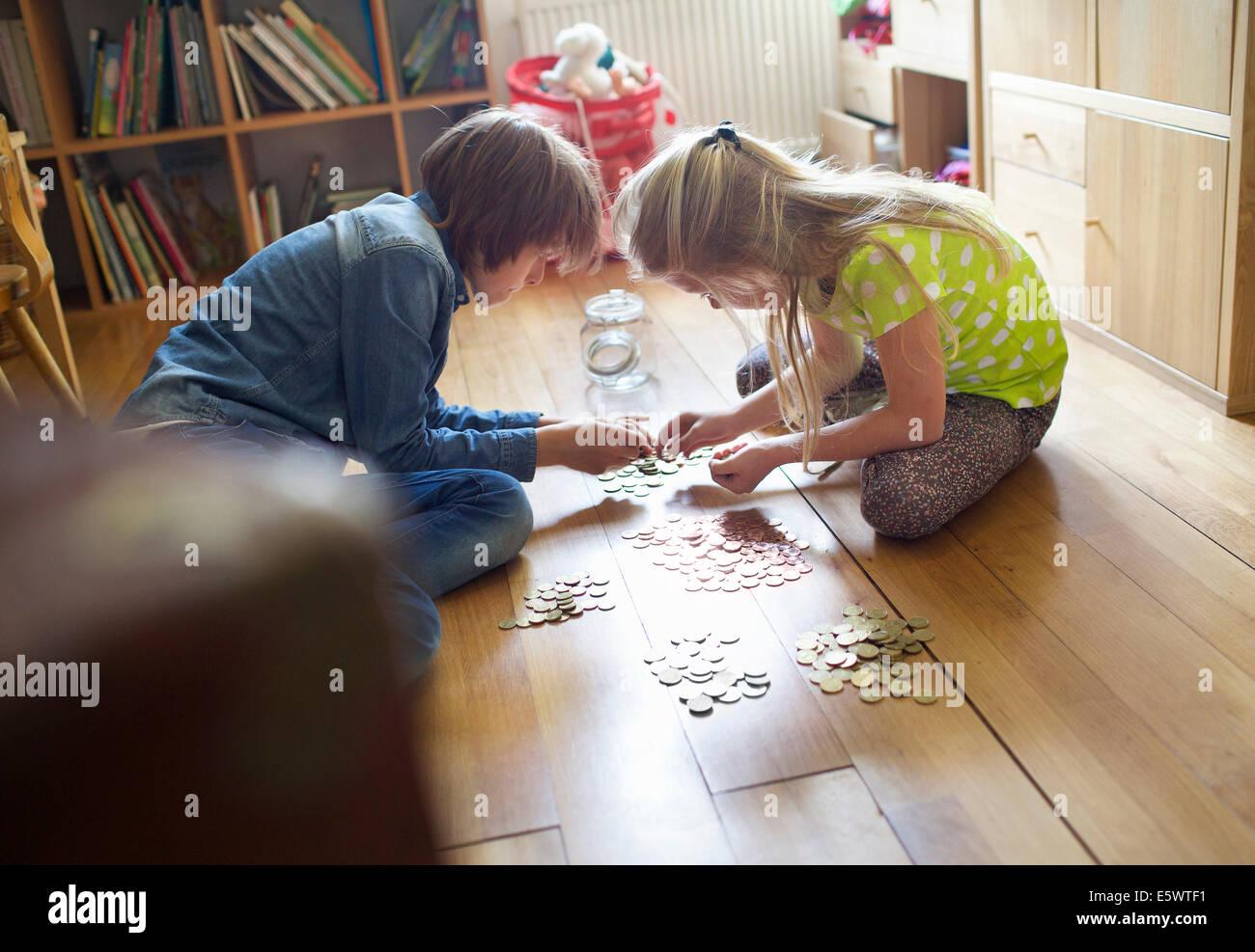 Fratello e Sorella il conteggio delle monete dal vaso di risparmio Immagini Stock