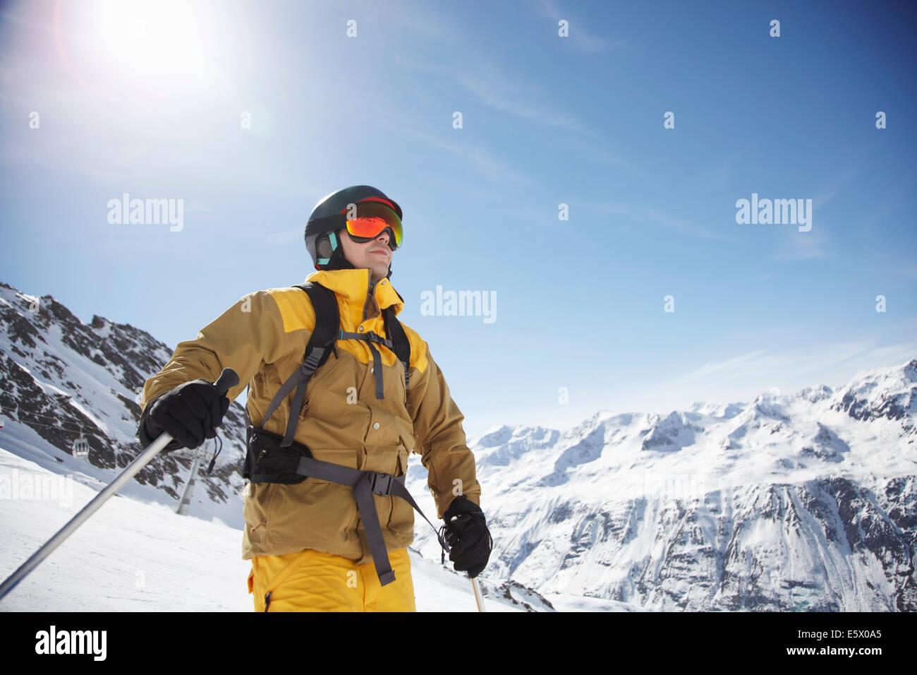 Basso angolo vista di metà maschio adulto sciatore sulla montagna, Austria Foto Stock