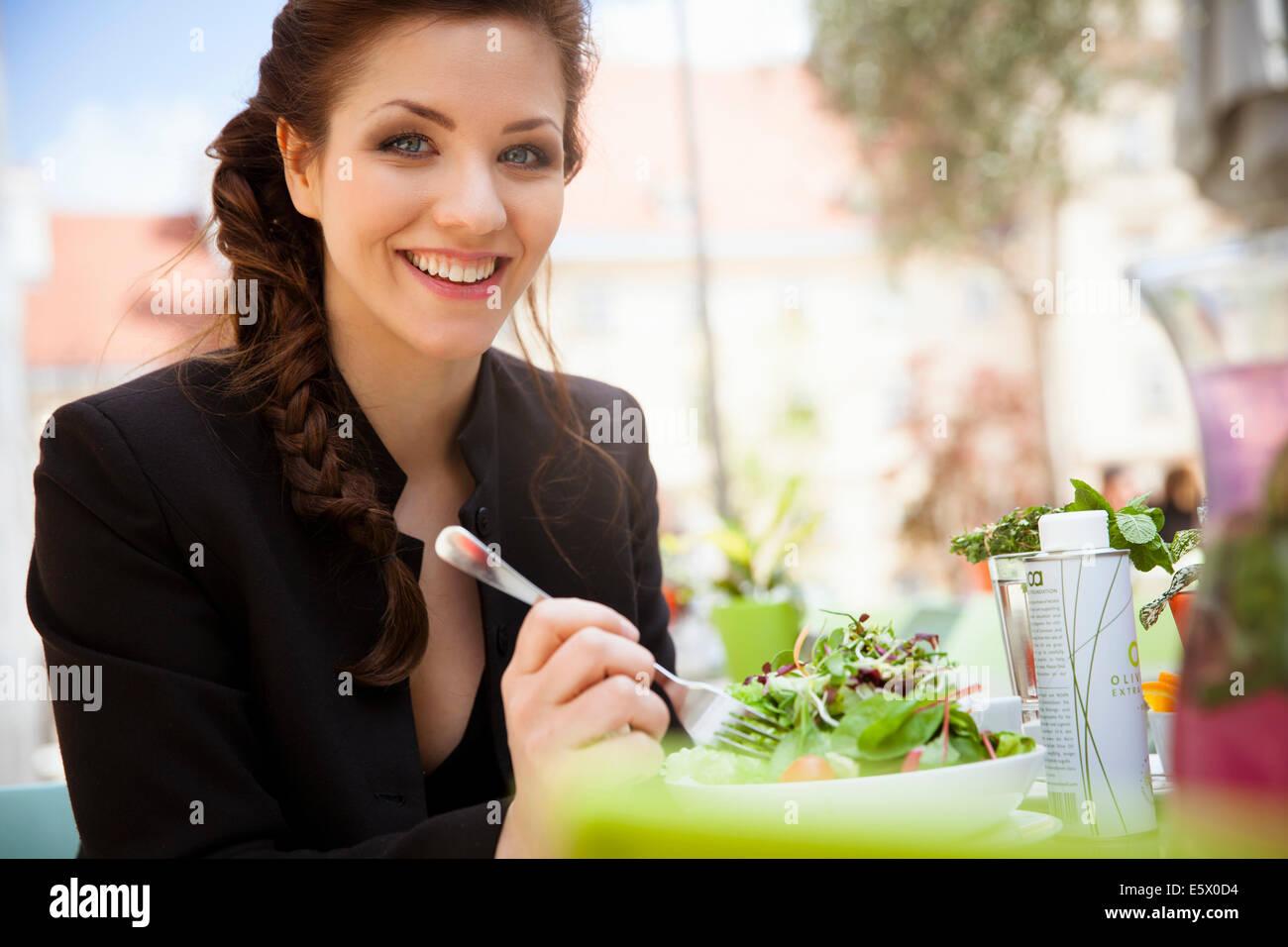 Giovane donna adulta mangiare insalata, esterno Immagini Stock