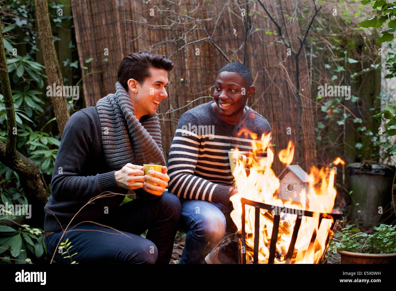 Due giovani uomini accovacciato davanti al fuoco del giardino con caffè Immagini Stock