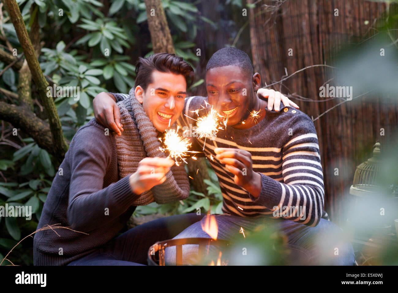 Due giovani uomini accovacciato nella parte anteriore del giardino il fuoco con le botti Immagini Stock