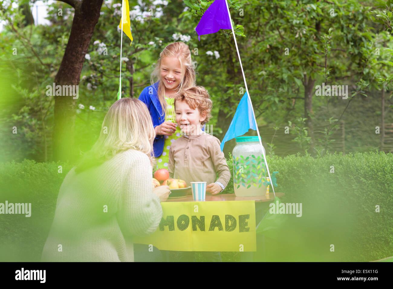 Madre acquisto di limonata dalla figlia di stand Immagini Stock
