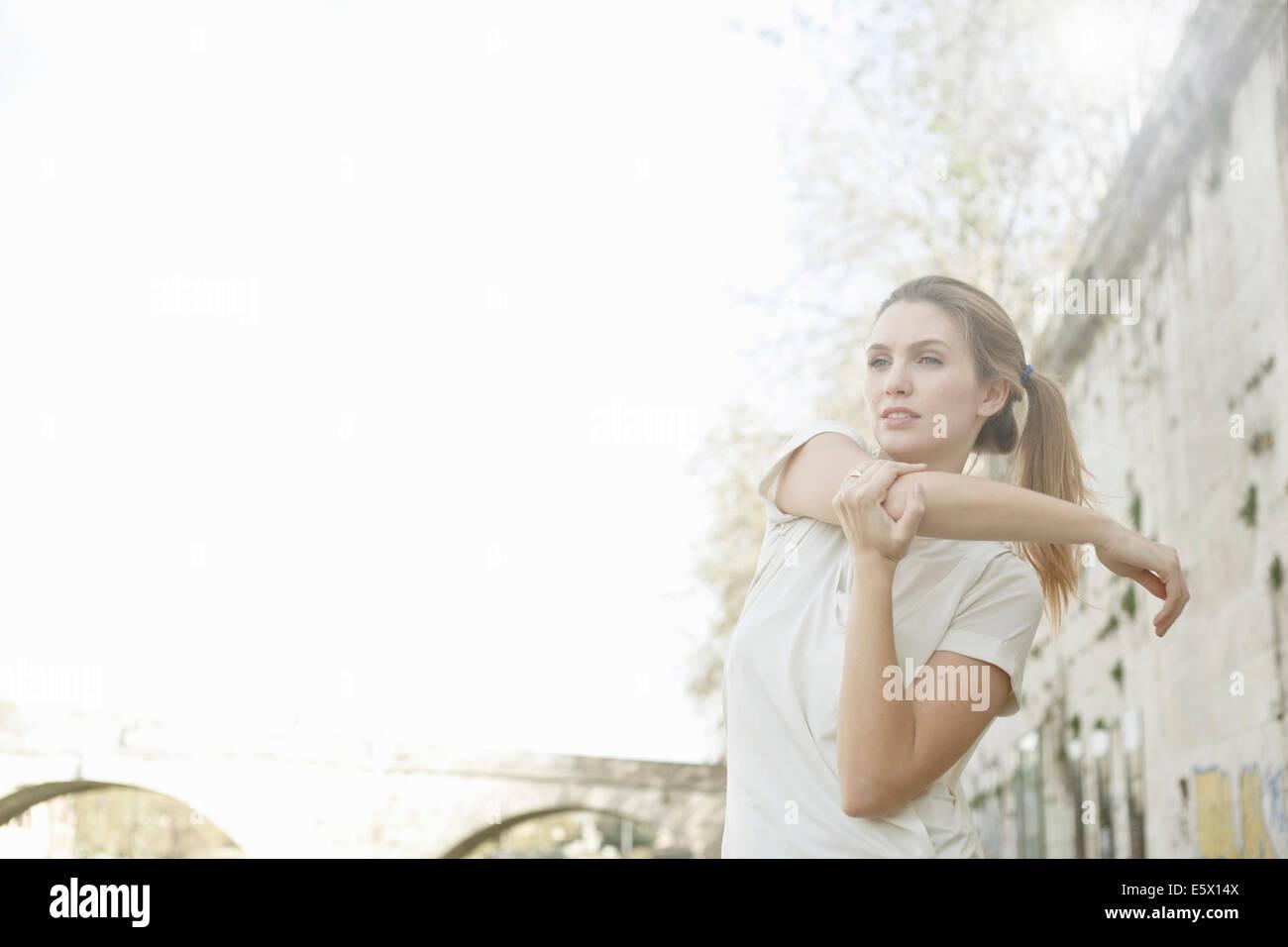 Giovane donna stretching braccio prima di esercizio Immagini Stock