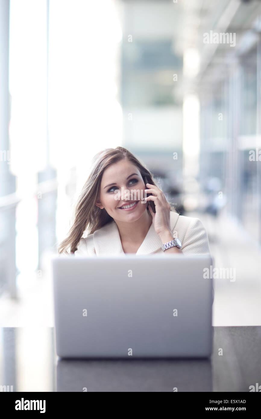 Giovane imprenditrice utilizzando laptop e chattare su smartphone nel centro congressi Immagini Stock