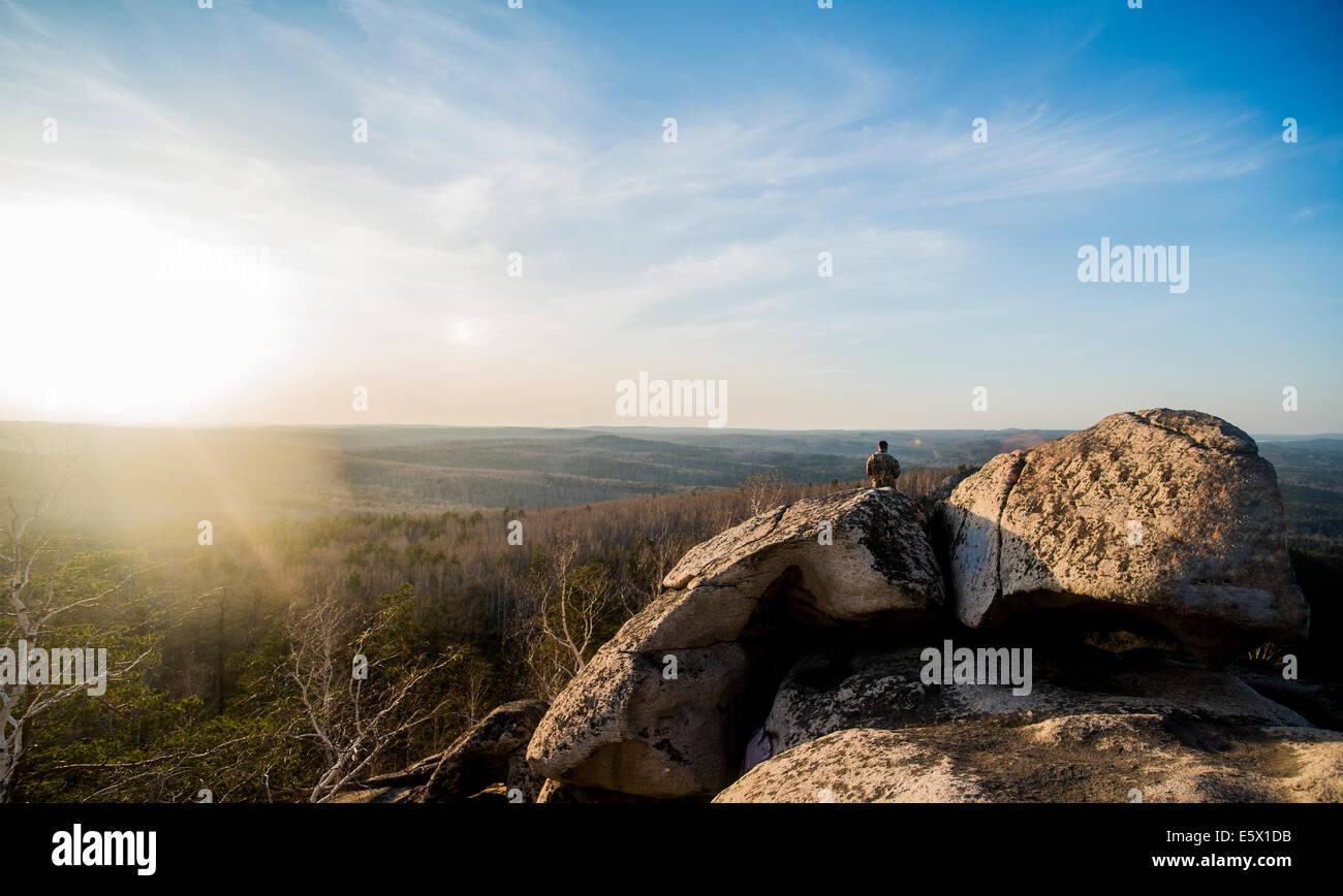 Giovane maschio escursionista sulla parte superiore di formazione di roccia Immagini Stock