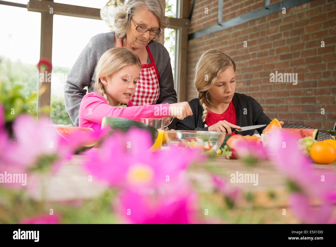 Due sorelle e la nonna al tavolo da cucina imparare ad affettare frutta fresca Immagini Stock