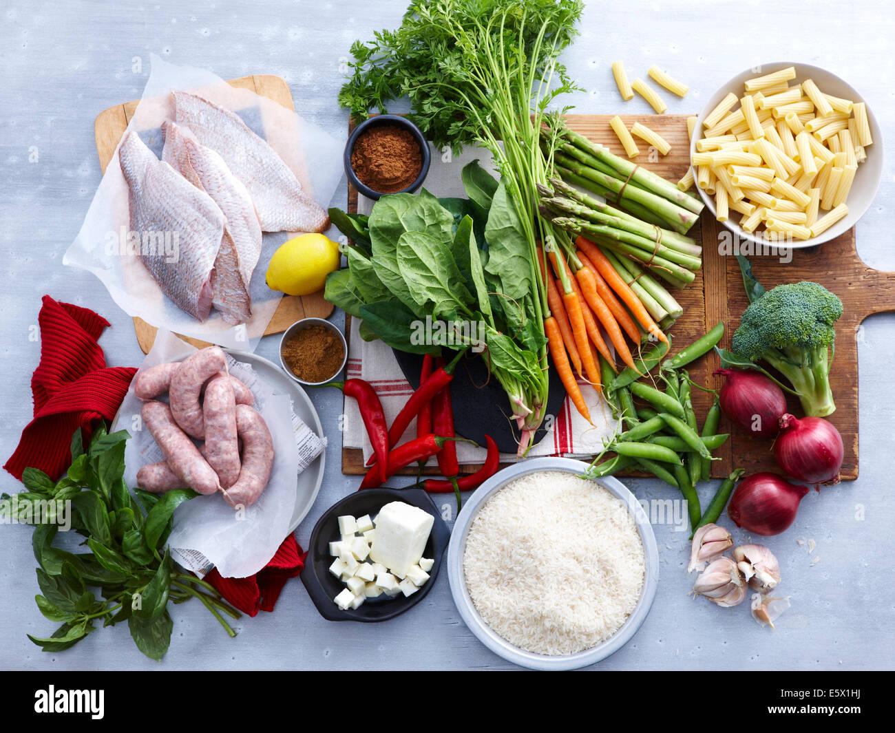 Vista aerea del pesce, salsicce di maiale, feta e una selezione di fresche le erbe e verdure Immagini Stock